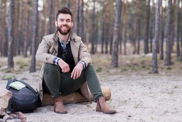 Portret uśmiechnięty męski podróżnika obsiadanie na plaży z jego plecakiem