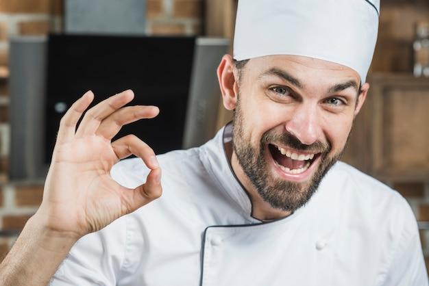 Portret uśmiechnięty męski szef kuchni pokazuje ok znaka