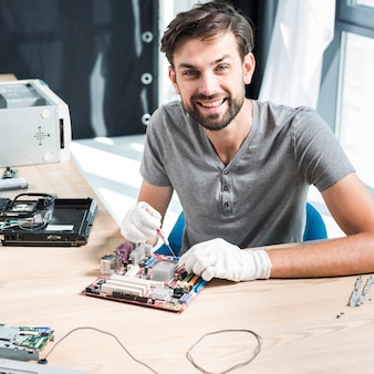 Portret uśmiechnięty męski technik naprawia komputerową płytę główną