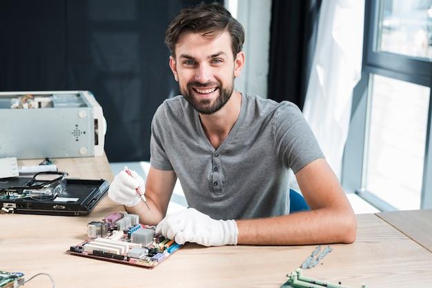 Portret uśmiechnięty męski technik pracuje na komputerowej płycie głównej