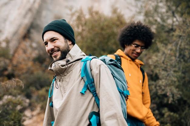 Portret uśmiechnięty męski wycieczkowicz wycieczkuje z jego przyjacielem