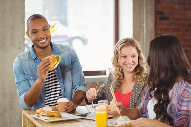 Portret uśmiechnięty mężczyzna ma hamburger z kolegami