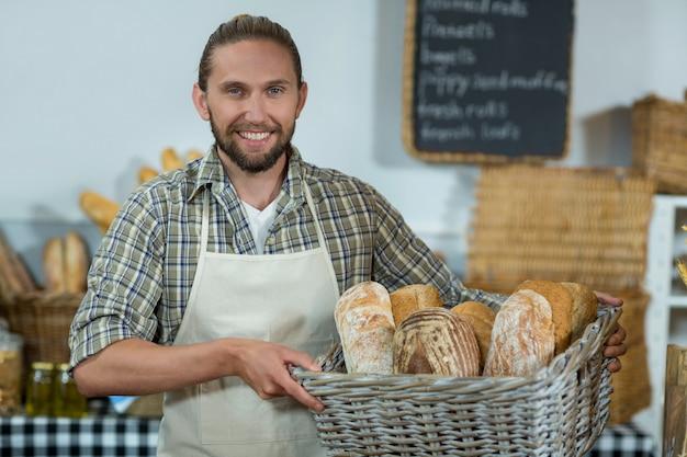 Portret uśmiechnięty mężczyzna pracowników posiadających kosz bagietek przy ladzie