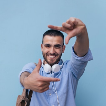 Portret uśmiechnięty mężczyzna robi ramie z jego ręką przeciw błękitnemu tłu