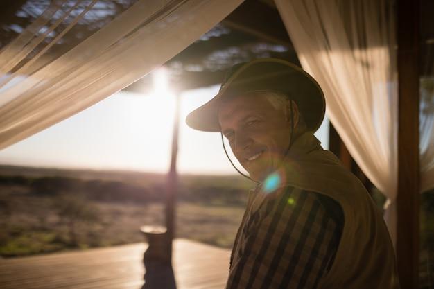 Portret uśmiechnięty mężczyzna siedzi na baldachimu łóżku