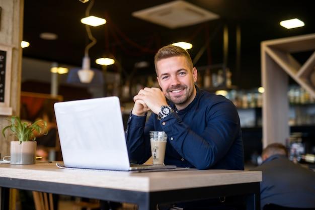 Portret uśmiechnięty mężczyzna siedzi w kawiarni z jego komputera przenośnego