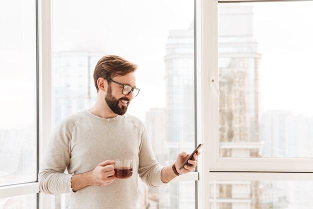 Portret uśmiechnięty mężczyzna używa telefon komórkowego