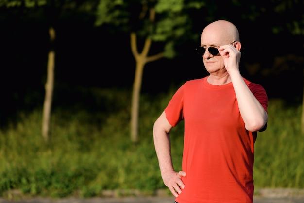 Portret uśmiechnięty mężczyzna w okularach przeciwsłonecznych i odwracając wzrok na ulicach miasta.