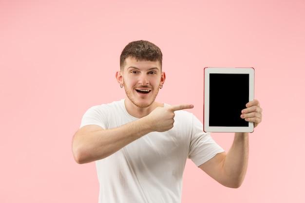 Portret uśmiechnięty mężczyzna, wskazując na laptopa z pustym ekranem na białym tle