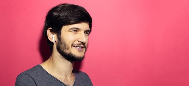 Portret uśmiechnięty mężczyzna z bezprzewodowymi słuchawkami na powierzchni różowego korala