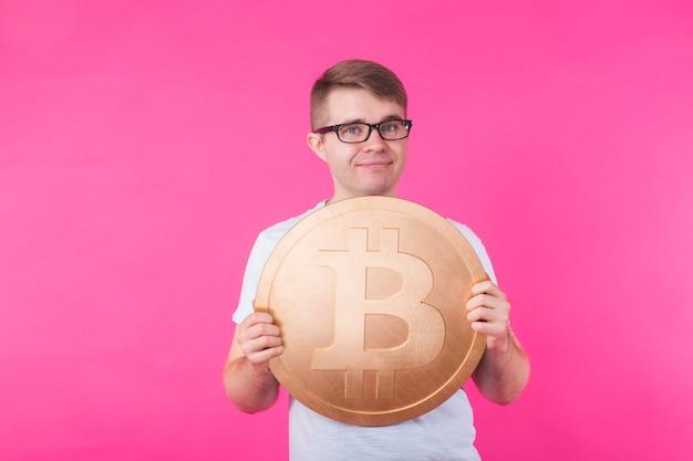 Portret uśmiechnięty mężczyzna z dużymi bitcoinami na różowej ścianie