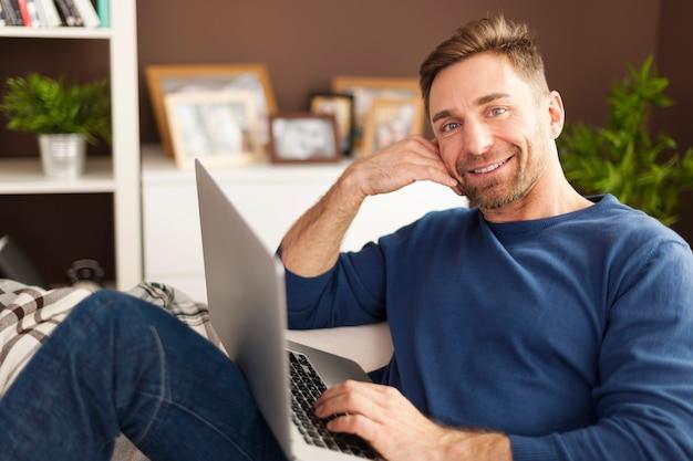 Portret uśmiechnięty mężczyzna z laptopem na kanapie