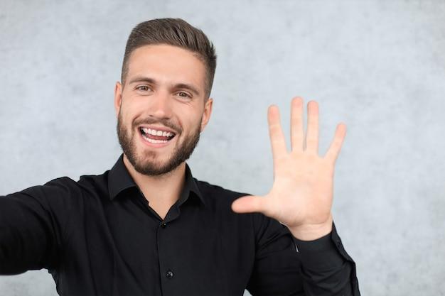 Portret uśmiechnięty mężczyzna z ręką podniesioną na powitanie. koncepcja piątki.