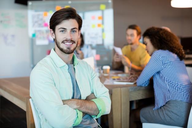 Portret uśmiechnięty mężczyzna z rękami skrzyżowanymi w biurze