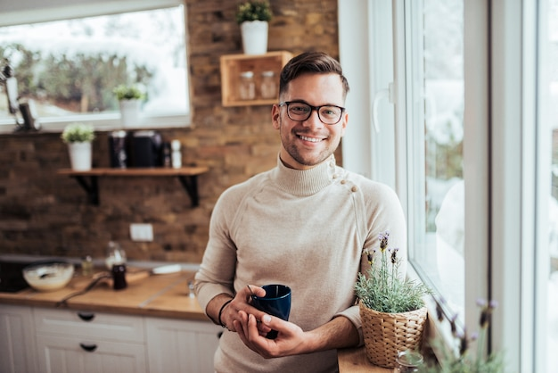 Portret uśmiechnięty millenial mężczyzna pije herbaty blisko okno przy wygodnym domem na zima ranku.