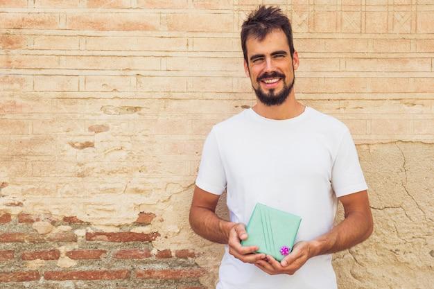 Portret uśmiechnięty młodego człowieka mienia prezent przeciw wietrzejącej ścianie