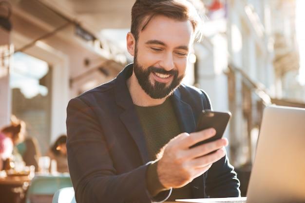 Portret uśmiechnięty młodego człowieka mienia telefon komórkowy