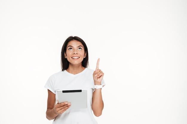 Portret uśmiechnięty młodej kobiety mienia pastylki komputer