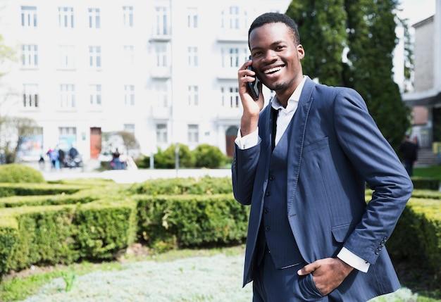 Portret uśmiechnięty młody afrykański biznesmen opowiada na telefonie komórkowym