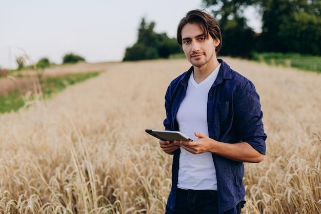 Portret uśmiechnięty młody agronom stoi w pszenicznym polu z ipad