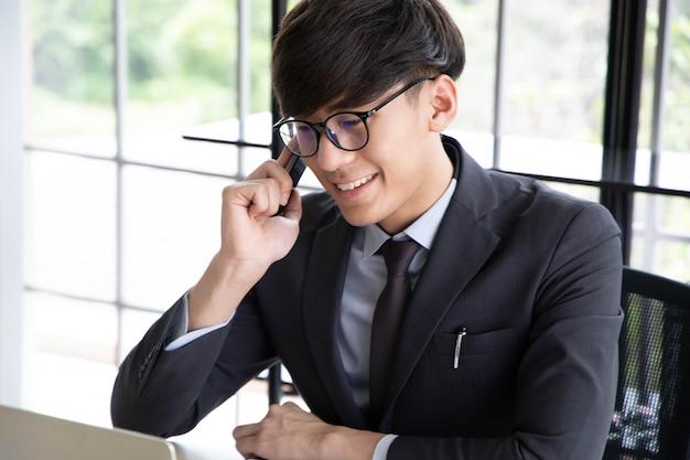 Portret uśmiechnięty młody biznesmen opowiada na jego smartphone podczas gdy pracujący, siedzący w jego biurze przy biurkiem jest ubranym czarnego kostium.