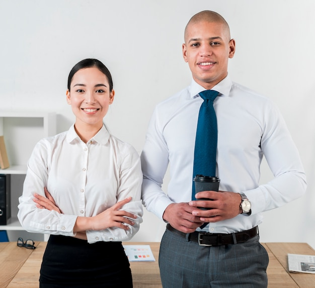 Portret uśmiechnięty młody biznesmen trzyma rozporządzalną filiżankę w ręki pozyci z bizneswomanem