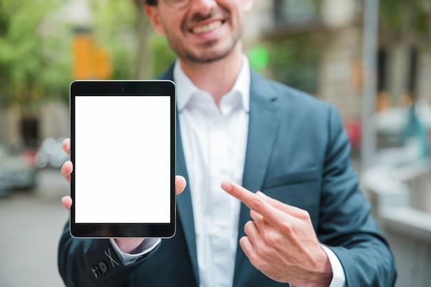Portret uśmiechnięty młody biznesmen wskazuje jego palec w kierunku cyfrowej pastylki