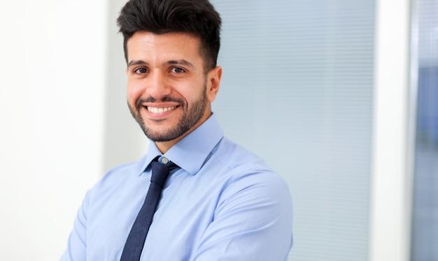 Portret uśmiechnięty młody biznesmena obsiadanie w jego biurze