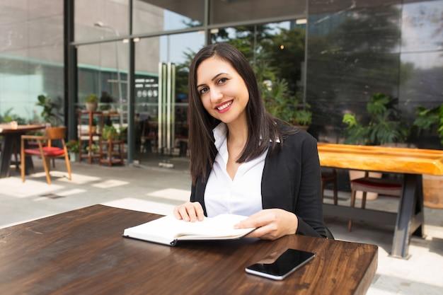 Portret uśmiechnięty młody bizneswoman lub uczeń przy kawiarnią