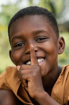 Portret uśmiechnięty młody chłopiec afryki robi cichy znak