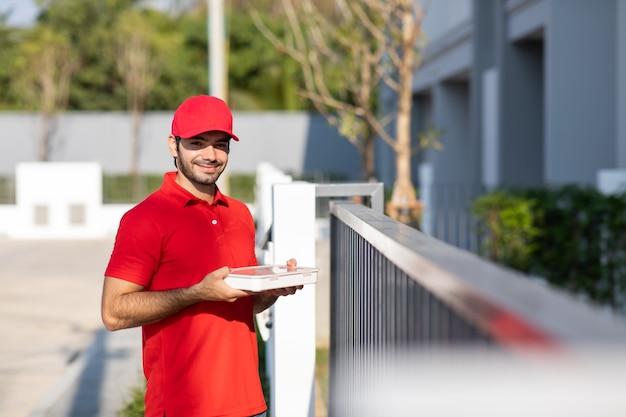 Portret uśmiechnięty młody człowiek dostawy w czerwonym mundurze trzyma pudełko przed domem.
