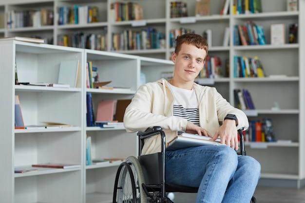 Portret uśmiechnięty młody człowiek na wózku inwalidzkim w bibliotece szkolnej i