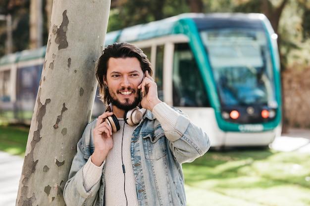 Portret uśmiechnięty młody człowiek opowiada na telefonie komórkowym przeciw zamazanemu autobusowi