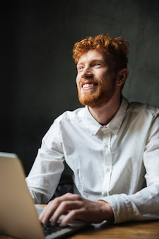 Portret uśmiechnięty młody człowiek pisać na maszynie na laptopie