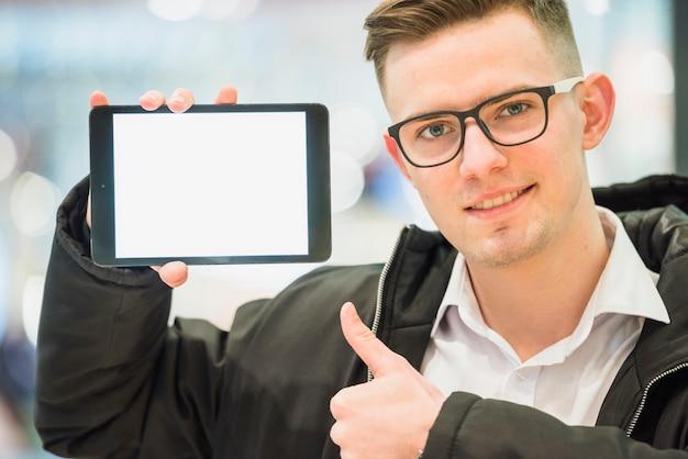 Portret uśmiechnięty młody człowiek robi kciukowi up gestowi pokazuje cyfrową pastylkę