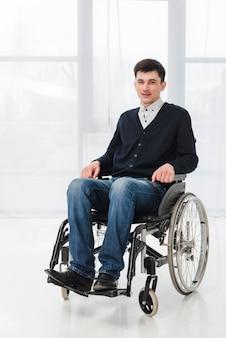 Portret uśmiechnięty młody człowiek siedzi na wózku inwalidzkim, patrząc na kamery
