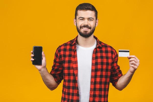Portret uśmiechnięty młody człowiek trzyma pustego ekranu telefon komórkowego i pokazuje kredytową kartę odizolowywająca nad kolor żółty ścianą.
