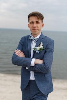 Portret uśmiechnięty młody człowiek w białej szarości i koszula nadaje się outdoors przy tłem nieba i morza