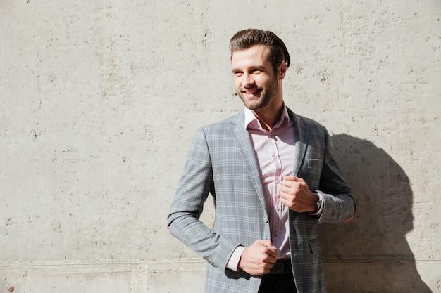 Portret uśmiechnięty młody człowiek w kurtce pozuje daleko od i patrzeje