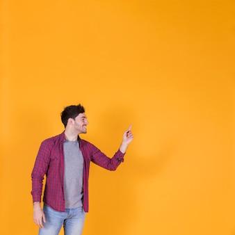 Portret uśmiechnięty młody człowiek wskazuje jego palec na pomarańczowym tle