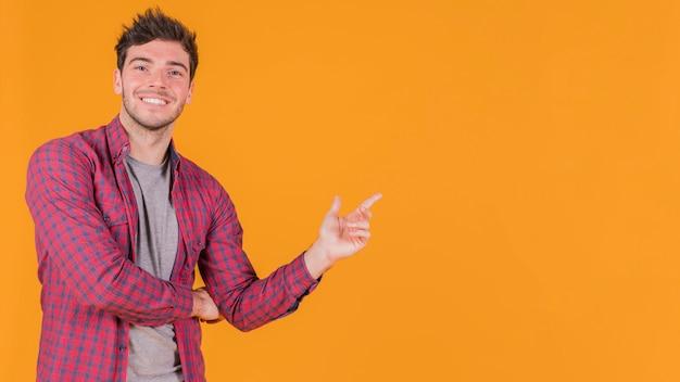 Portret uśmiechnięty młody człowiek wskazuje jego palec przy coś przeciw pomarańczowemu tłu