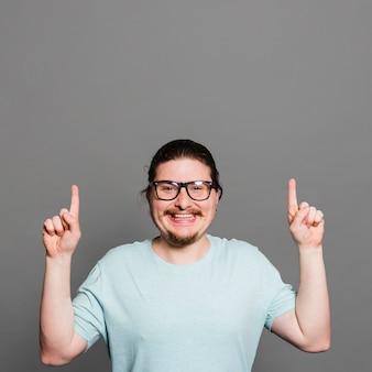 Portret uśmiechnięty młody człowiek wskazuje palce oddolny patrzejący kamerę