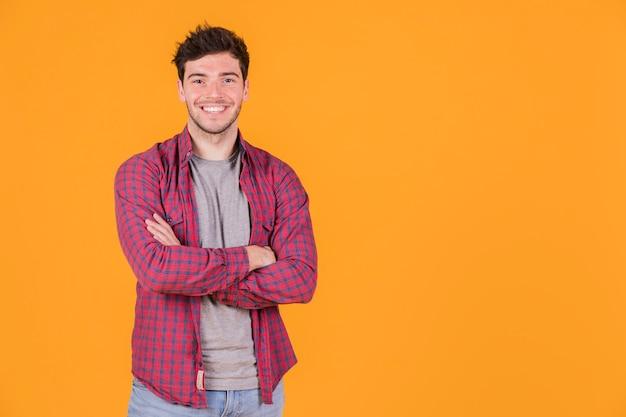 Portret uśmiechnięty młody człowiek z jego rękami krzyżował patrzeć kamerę