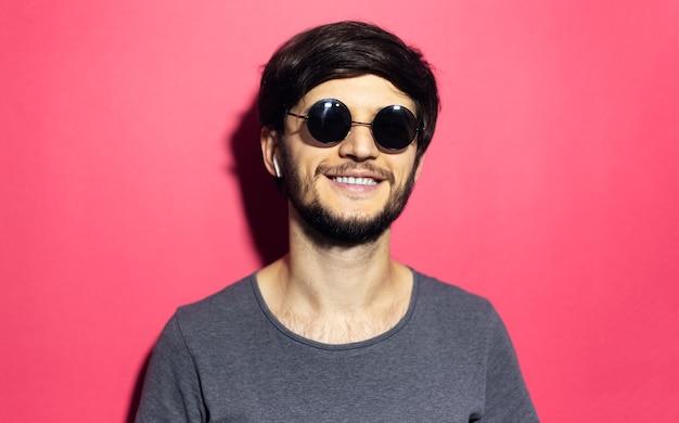 Portret uśmiechnięty młody człowiek z okulary i słuchawki bezprzewodowe na białym tle na powierzchni różowego korala