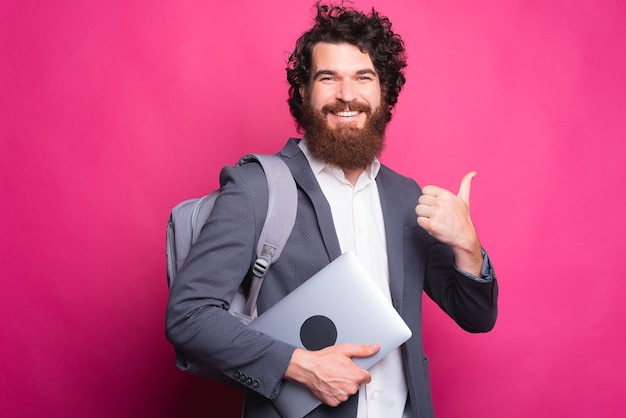Portret uśmiechnięty młody człowiek z plecakiem i trzymając laptop i pokazując kciuk do góry