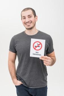 Portret uśmiechnięty młody człowiek z ręką w jego kieszeni pokazuje palenie zabronione znaka