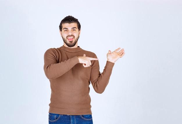 Portret uśmiechnięty młody facet, wskazując na jego dłoń. zdjęcie wysokiej jakości
