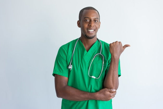 Portret uśmiechnięty młody lekarz wskazuje przy coś z kciukiem.