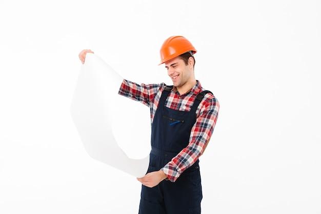 Portret uśmiechnięty młody męski budowniczy egzamininuje papierowego szkic