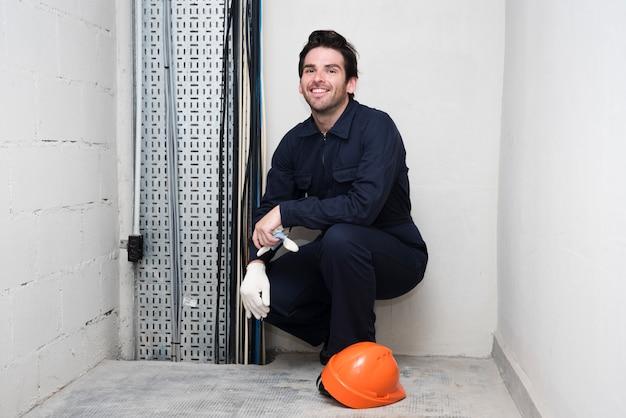 Portret uśmiechnięty młody męski elektryk przy miejscem pracy